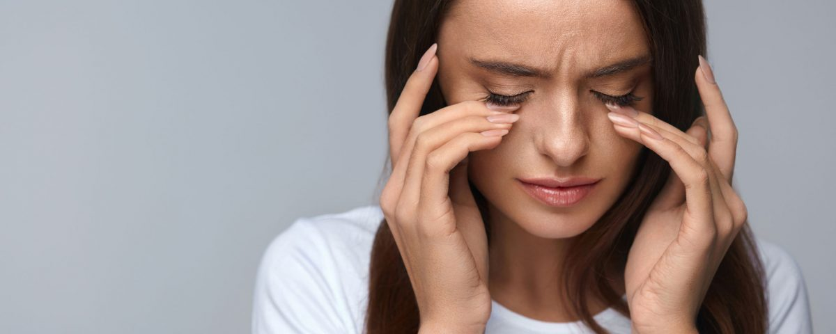 Someone with squinting, headaches, light sensitivity, and visual distortions: signs you need to schedule an eye exam.
